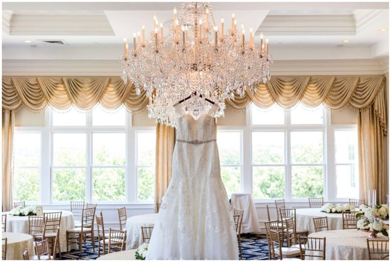 Wedding Gown hanging from custom hanger on chandelier in the ballroom at a Trump National Philadelphia wedding.