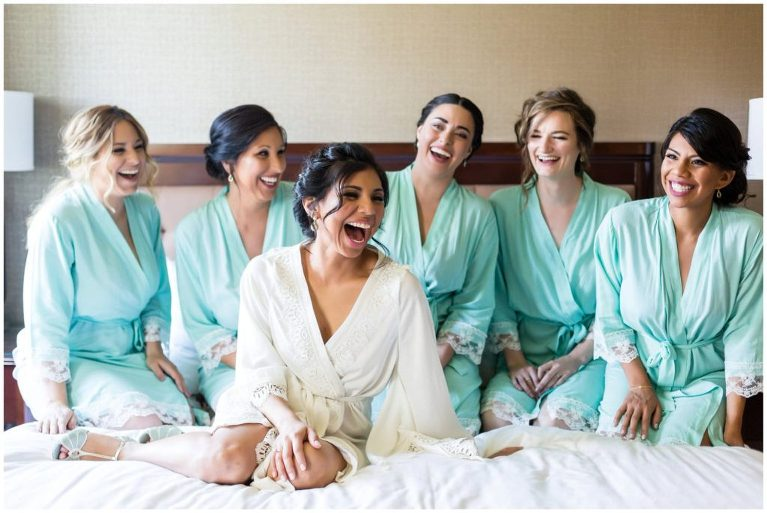 Bride with her bridesmaids in matching turquoise robes while the get ready for their Historic Penn Farm Wedding.