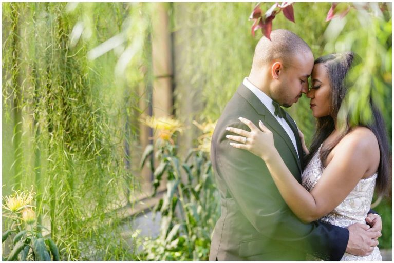 Shooting through the greenery during a Longwood Gardens engagement session can create a sense of intimacy in the pose and visual interest in the portrait.