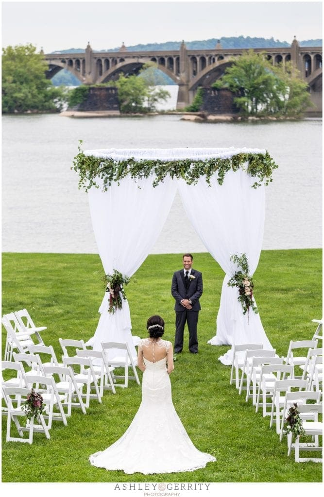 Outdoor wedding ceremony along Susquehanna River at John Wright Restaurant in Wrightsville, PA featuring design by Shumaker PDT