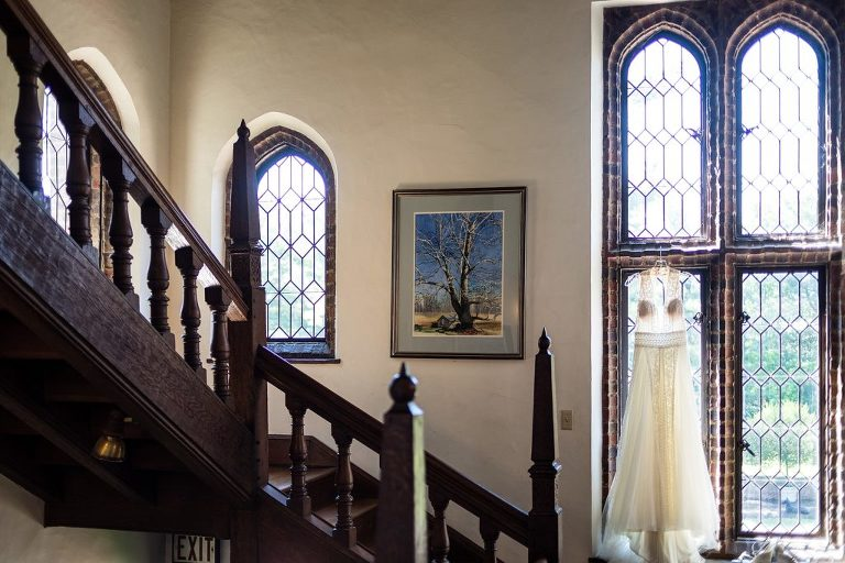 wedding dress hanging in window, mansion, mansion wedding, donna morello, lace wedding dress, open back wedding dress