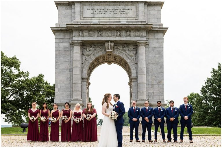 traditional bridal party portrait with maroon and navy color palette at Valley Forge Park Archway