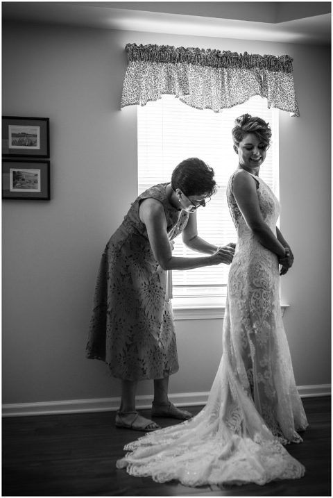 Black and white portrait of the mother of the bride buttoning brides gown