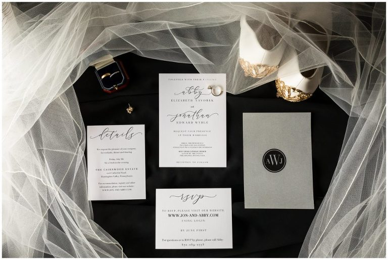 Wedding invitation suite layout with earrings, wedding bands, shoes, and veil