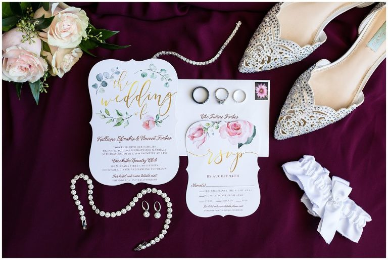 Floral wedding invitation suite with bridal shoes, jewelry, garter, and florals