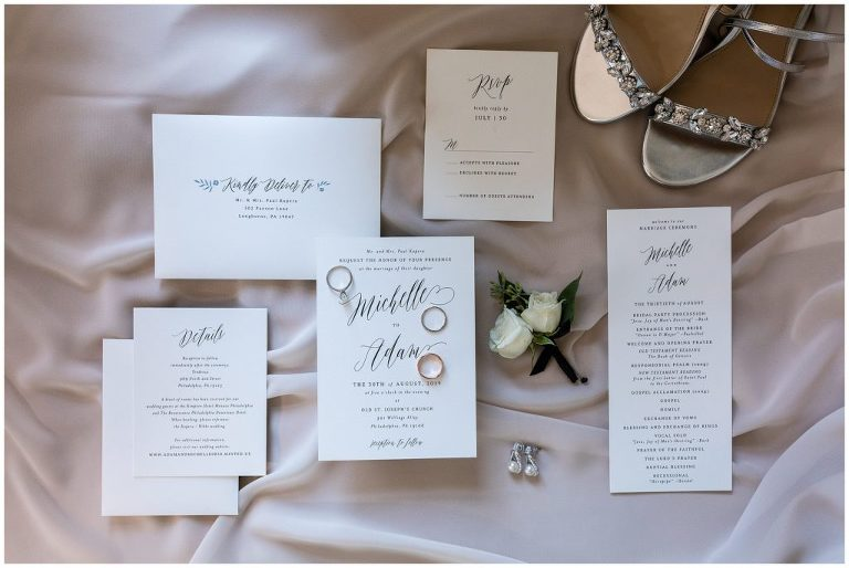 Simple black and white wedding invitation suite with wedding rings, earrings, shoes, and florals