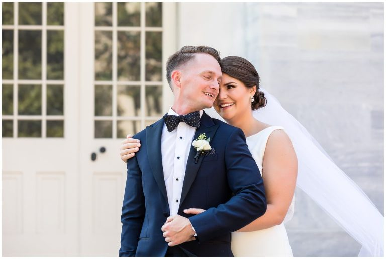 Bride and groom holding each other and laughing portrait