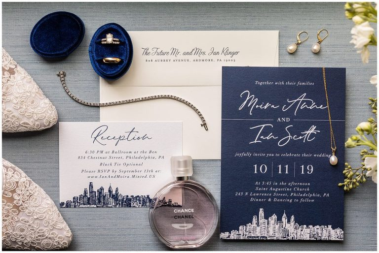 Navy blue and white wedding invitation suite with Philadelphia skyscrapers, wedding shoes, wedding bands, jewelry, and perfume
