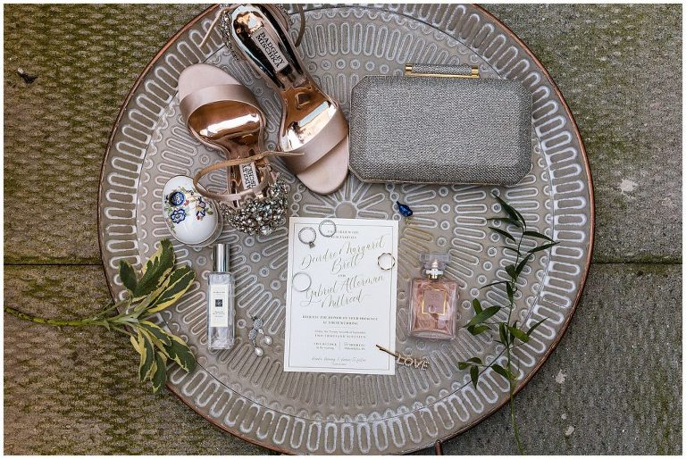 Golden and white wedding invitation with bridal accessories, purse, heels, perfume, wedding rings, and hair piece
