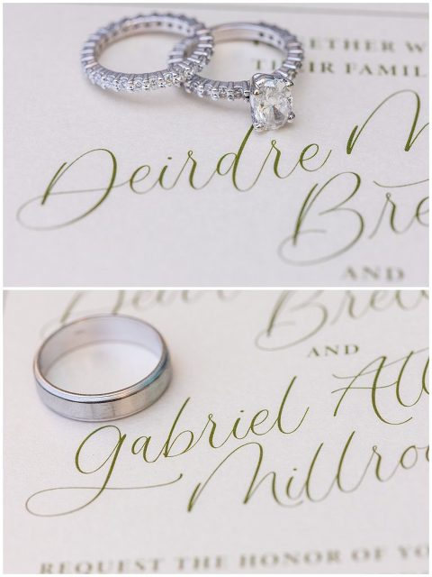 Wedding bands and engagement rings next to bride and grooms name on wedding invitation