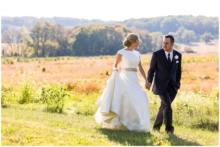 Bride and groom walking together through Valley Forge National Park