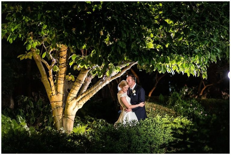 dramatic nighttime portrait of bride and groom in the courtyard at the Radnor Hotel