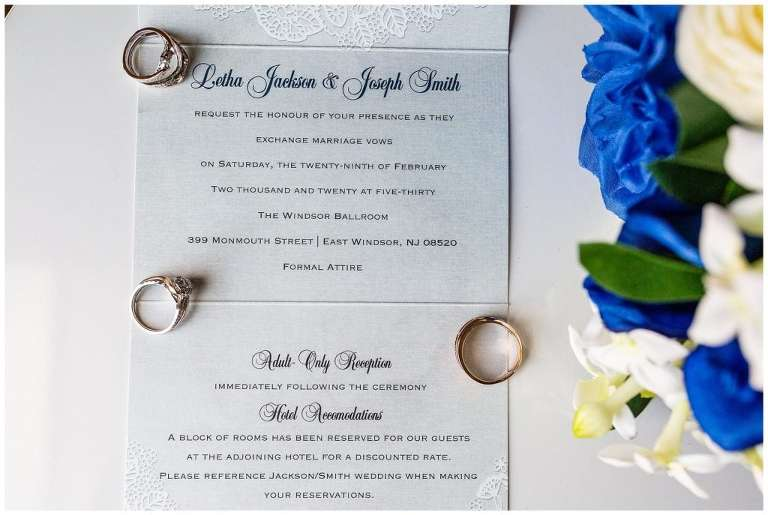 blue and lace invitation suite with wedding rings laid on top