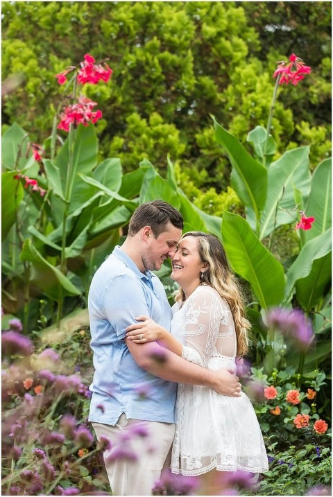 Couple embracing and laughing through flowers at Longwood Gardens engagement portrait session