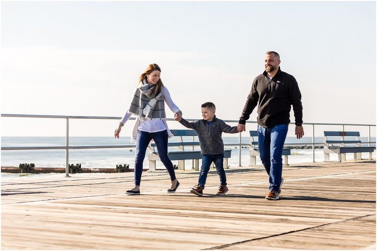 Couple holding hands with child walking down Ocean City New Jersey Boardwalk engagement session