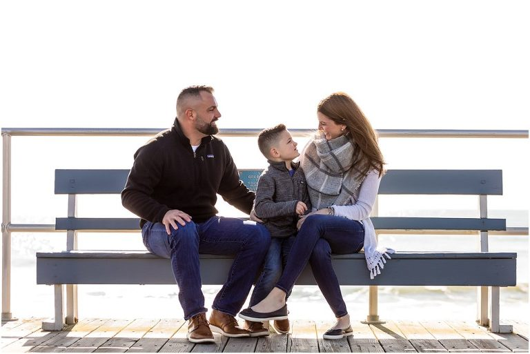 Couple sits on bench and laughs with son on Ocean City New Jersey Boardwalk engagement session