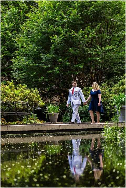 Classic engagement session portrait walking by pond with reflection at Winterthur